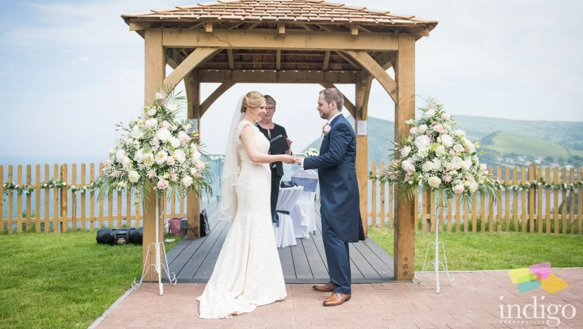 a picture of a couple getting married with two bouquets of flower and a background sea view