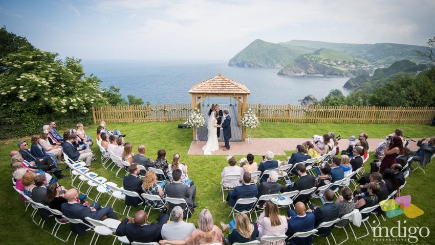 a picture of a couple getting married with family outside, with the sea and cliffs in the background