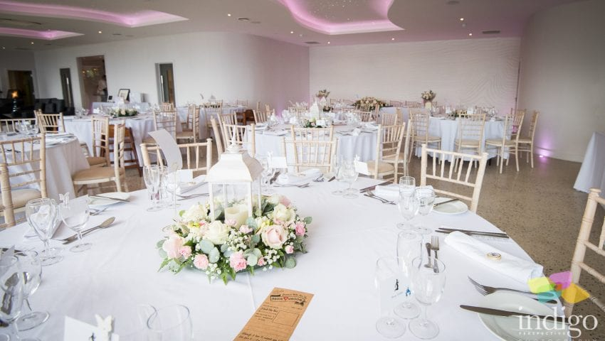 a picture of a wedding dining room with white laid tables and floral centerpieces