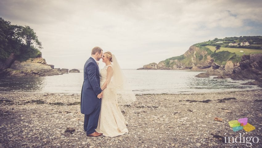 a picture of a bride and groom holding each other on a stone beach with the sea in the background