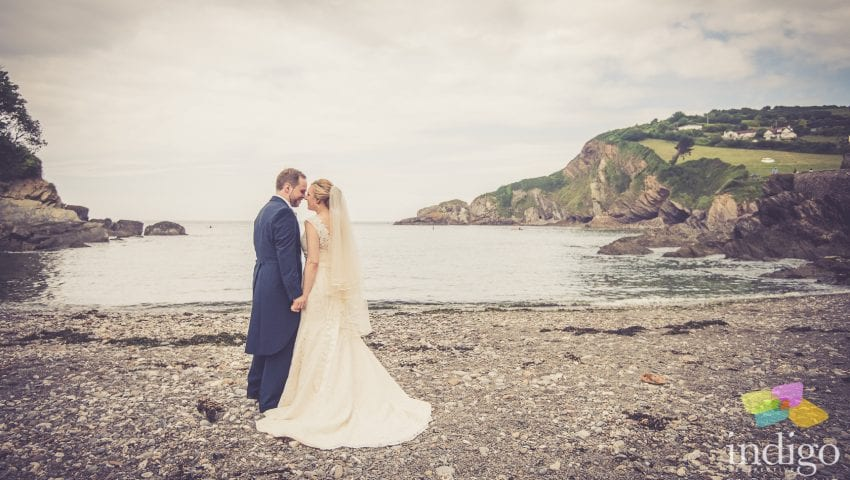 a picture of a bride and groom facing each other on a stone beach with the sea in the background