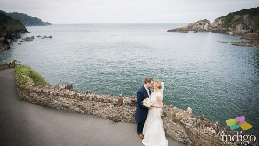 a picture of the bride and groom next to stone wall over the sea