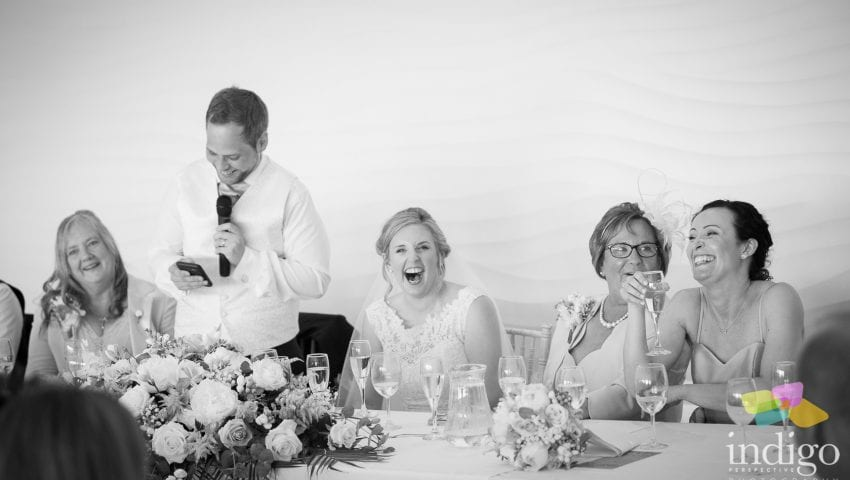 a black and white picture of the top table at the wedding where 5 people are laughing