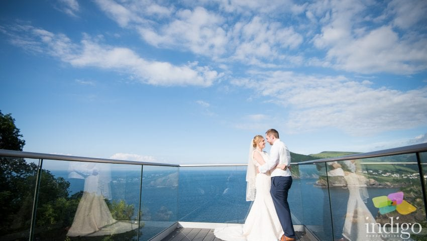 a picture of the bride and groom on the balcony with the sea and cliffs in the background