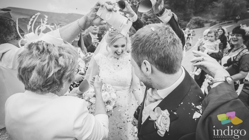 a black and white picture of a bride and groom having confetti thrown on them by family