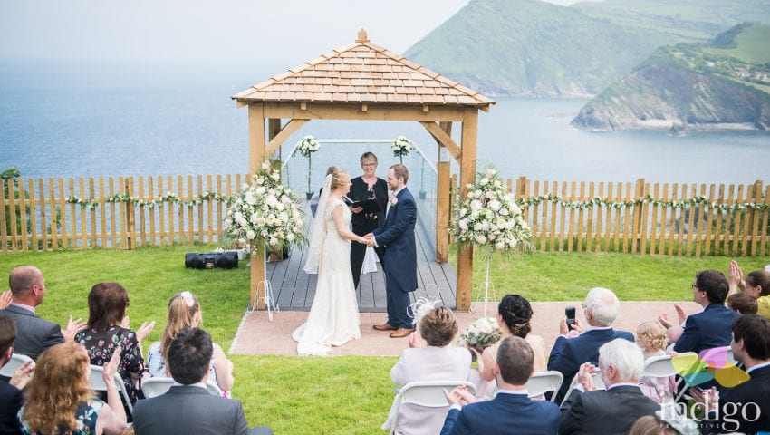 a picture of the bride and groom kissing infront of family outside, with the sea and cliffs in the background