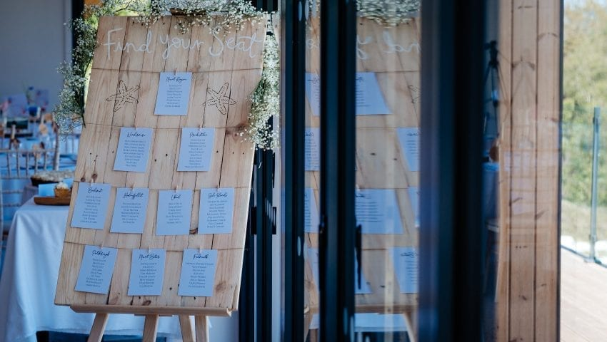 a picture of a wooden wedding find your seat sign