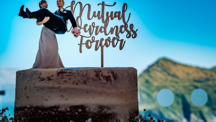 a picture of a wedding cake with cake toppers and a cliff and blue sky in the background