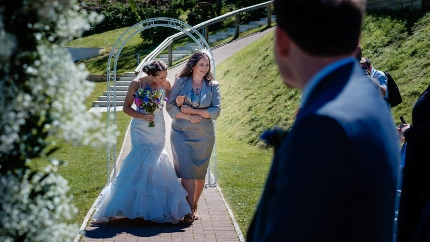 a picture of the bride being walked down the isle holding a bouquet