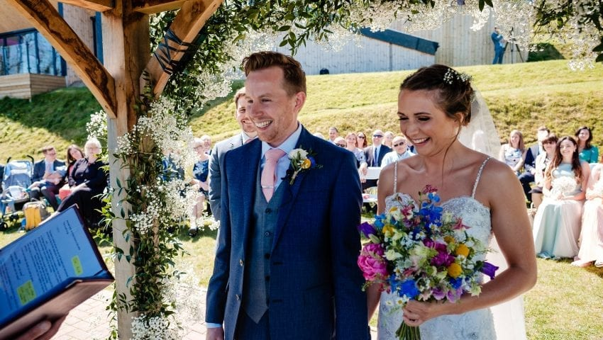 a picture of the bride and groom holding hands under the arch with their family in the background