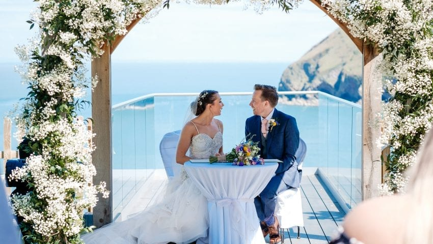 a picture of a bride and groom sat down on a white tables and chairs on the balcony looking at each other with the sea in the background
