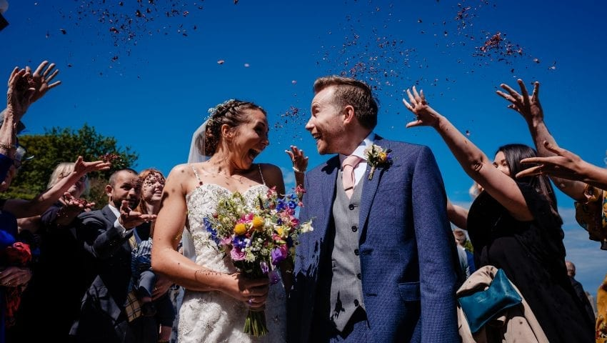 a picture of bride and groom walking through confetti being thrown by family