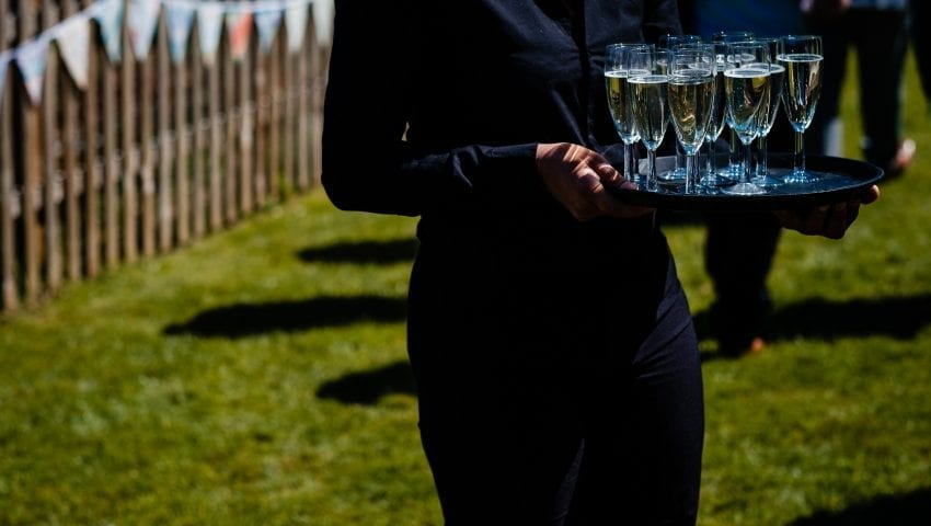 a picture of someone holding a tray of champagne