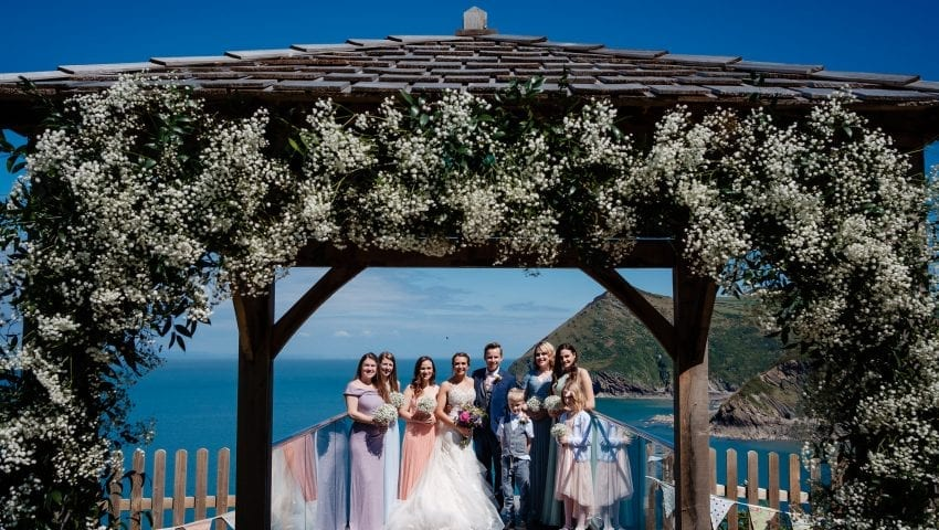 a wedding picture of a family standing on the balcony with the sea in the background