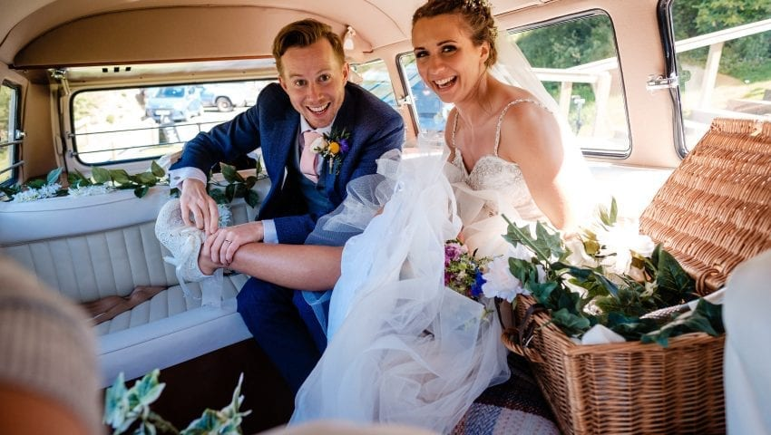 a picture of the bride and groom in the back of the wedding car smiling at the camera