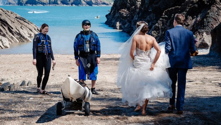 a picture of the bride and groom on a beach talking to rowers