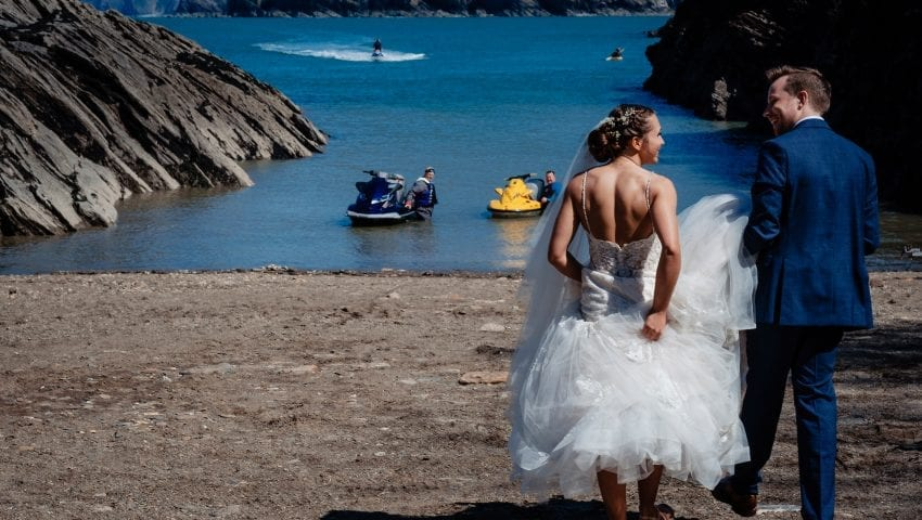 a picture of the bride and groom on the beach with the sea in the background with jet skis