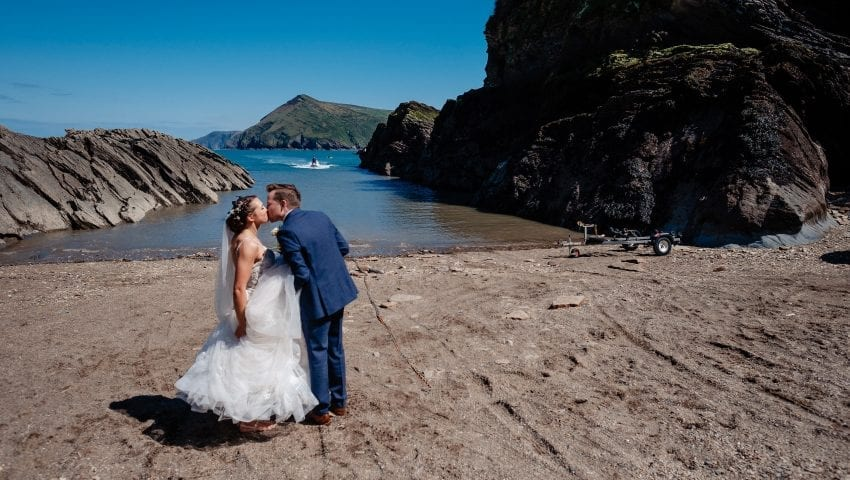 a picture of a bride and groom kissing on the beach with the sea in the background
