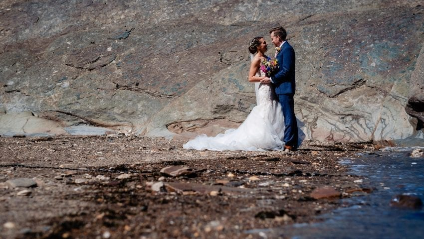 a picture of a bride and groom on the beach with large rock background