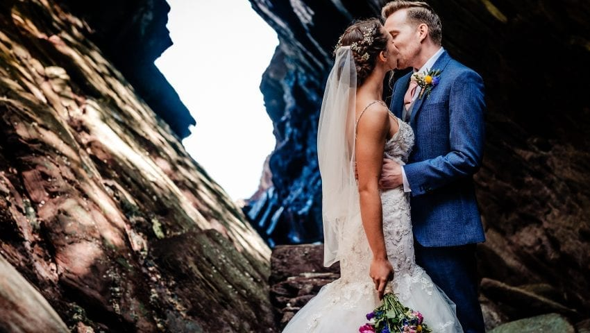 a picture of bride and groom kissing in front of a rock cave