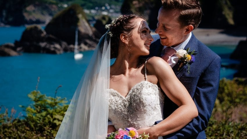 a picture of the bride and groom holding each other with a sea background