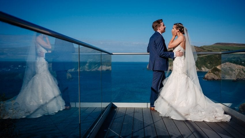 a picture of the bride and groom posing on the balcony in front of the sea