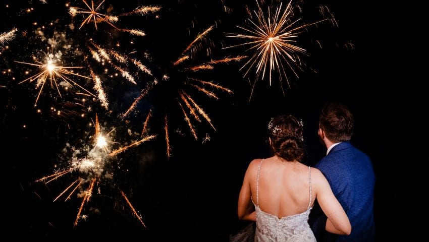a couple watching fireworks outside