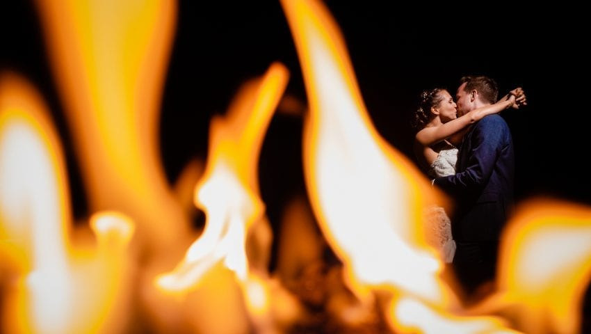 a picture of a couple kissing just behind a close up of flames