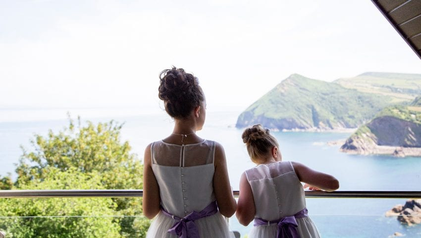 a picture of two young girls standing on the balcony in dresses