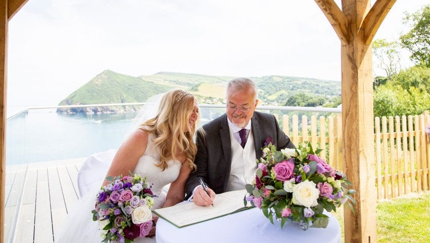 a picture of a couple signing the register with the sea and cliffs in the background
