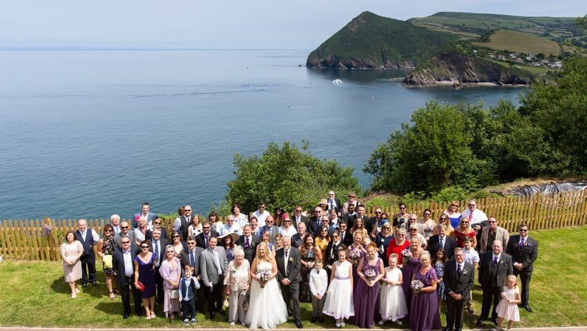 a picture of a group photo of wedding guests with the sea and trees in the background