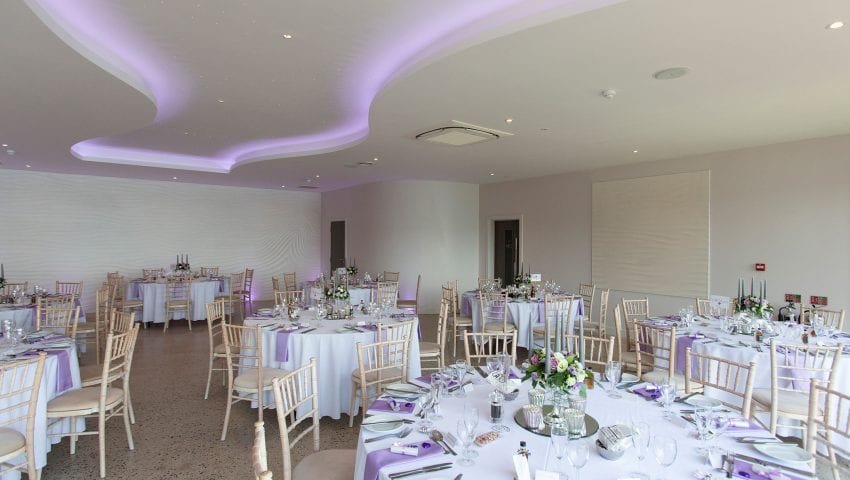 a picture of a wedding dining room with laid tables, with lilac accents