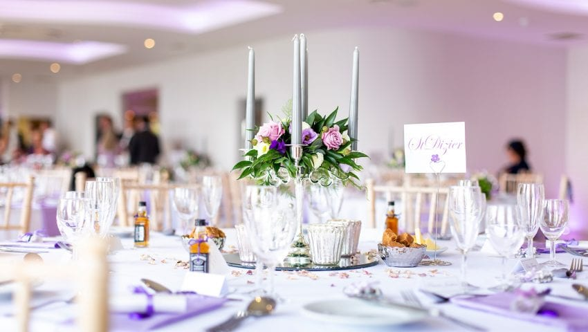 a picture of a laid wedding table with purple accents and favours