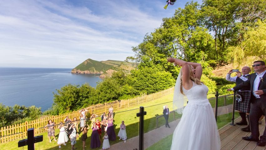 a picture of the bride throwing a bouquet over the balcony to the family below, sea and trees in the background