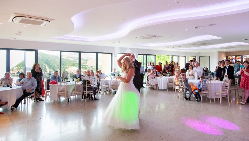 a picture of dining room with families at wedding tables watching the bride and groom dance in the middle of the room
