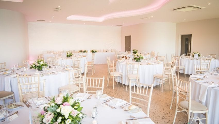 a picture of a wedding dining room with white laid tables, rose bouquets and wooden chairs