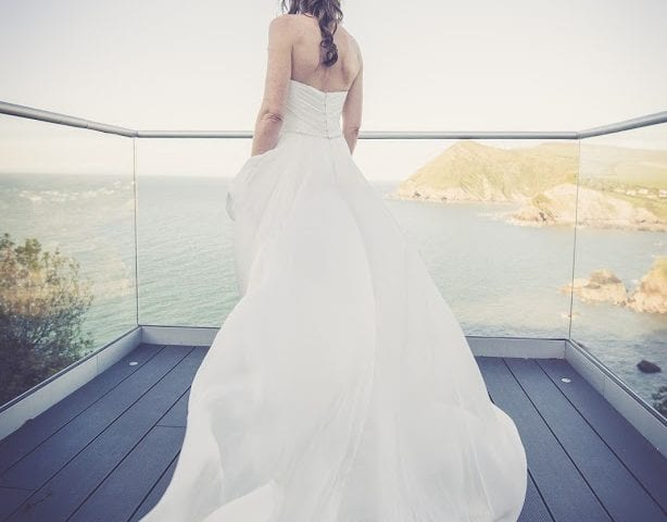 a picture of a bride on the balcony facing towards the sea and cliffs