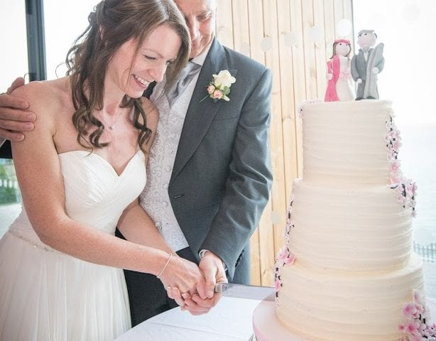 a picture of the bride and groom cutting their 3 tier cake