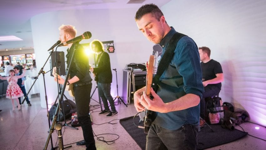 a picture of 4 members in a band playing music in a pink tinted room