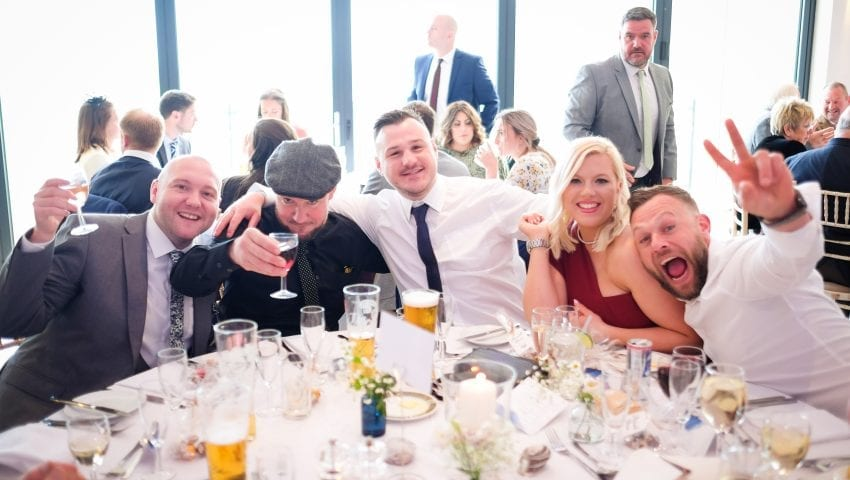 a picture of family at a wedding table with drinks