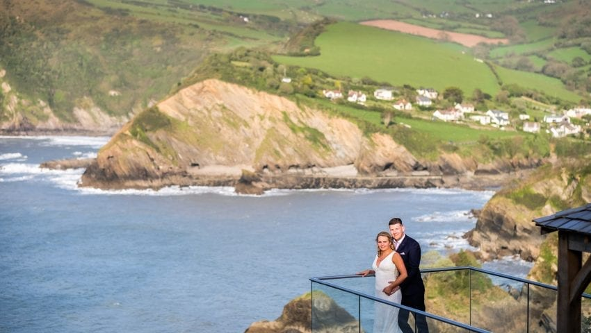 a picture of a married couple standing on the balcony overlooking the sea, cliffs and trees
