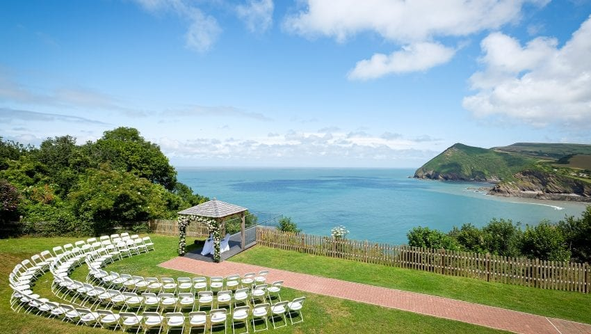 a picture overview of an outside wedding set up of a marriage arch, seating and an overlooking view of the sea and cliffs