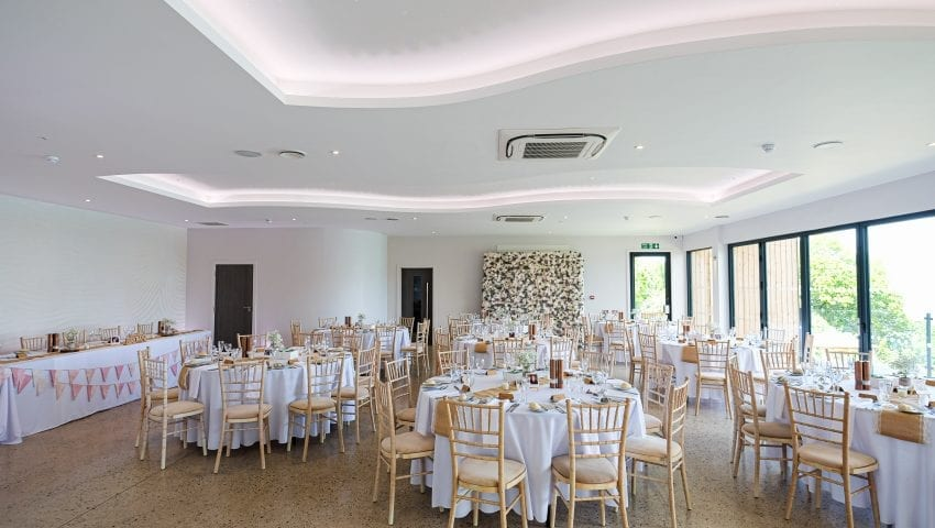 a picture of a wedding dining room with white laid tables and wooden chairs
