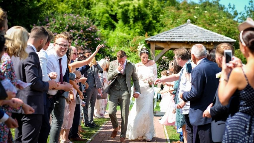 a picture of a bride and groom walking through scattered confetti in the middle of family
