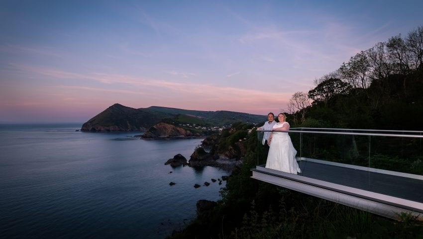 a picture of a couple standing on the balcony with the sea, cliffs and trees in the background