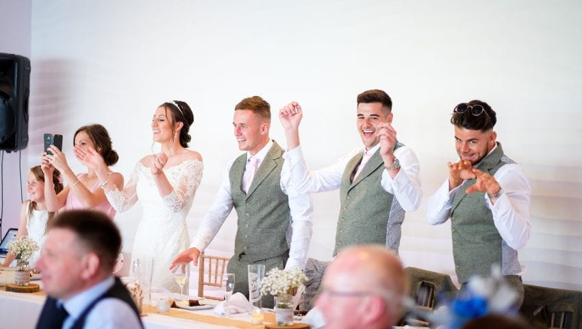 a picture of five people stood up at the top table with their hands in the air