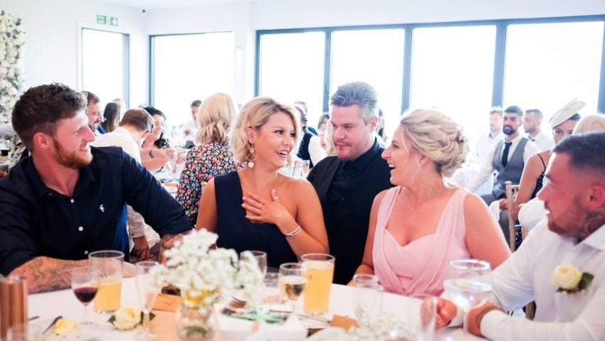 a picture of a room filled with family sat around tables with drinks at a wedding