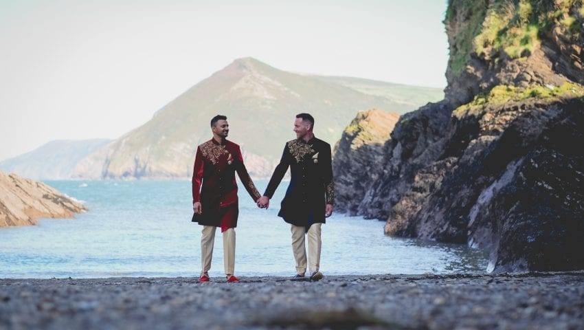 a picture of a couple holding hands walking on a stone beach with the sea and the cliffs in the background