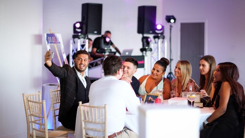 a picture of a group of people around a table at a wedding taking a selfie with a dj in the background