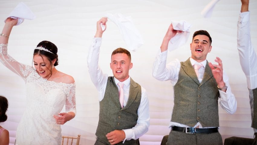 a picture of one bride, and two groomsmen holding their napkins up in the air